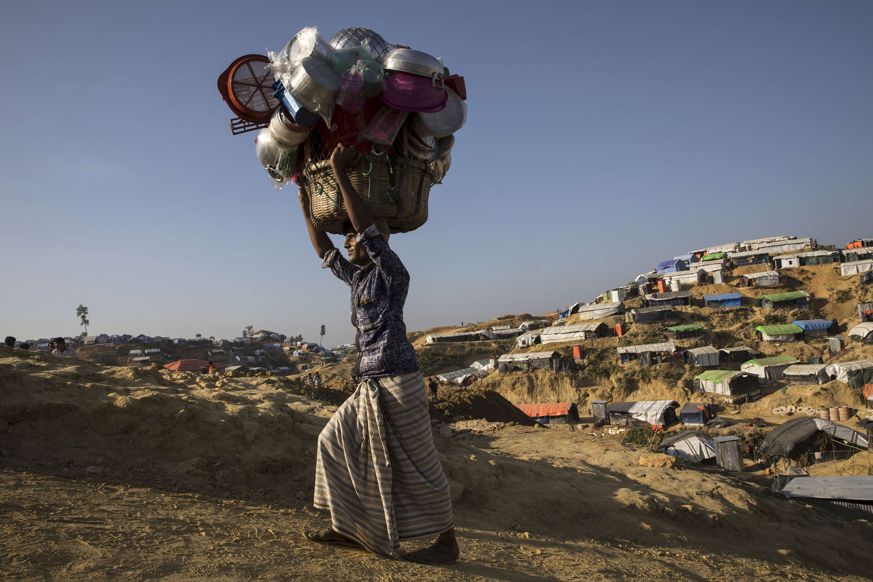 A man carries kitchen items for sale as he walks along Balukhali refugee camp.For years Buddhist majority Myanmar has struggled to deal with a deeply rooted hatred towards the Rohingya in western Rakhine state. The Muslim ethnic minority were always considered illegal immigrants from Bangladesh and denied the rights of citizenship. The refugee emergency unfolded in late August after an attack on state security forces by Rohingya insurgents, triggering a brutal military crackdown that has forced more than 650,00 of the country fleeing to neighboring Bangladesh creating the fastest cross-border exodus ever witnessed.