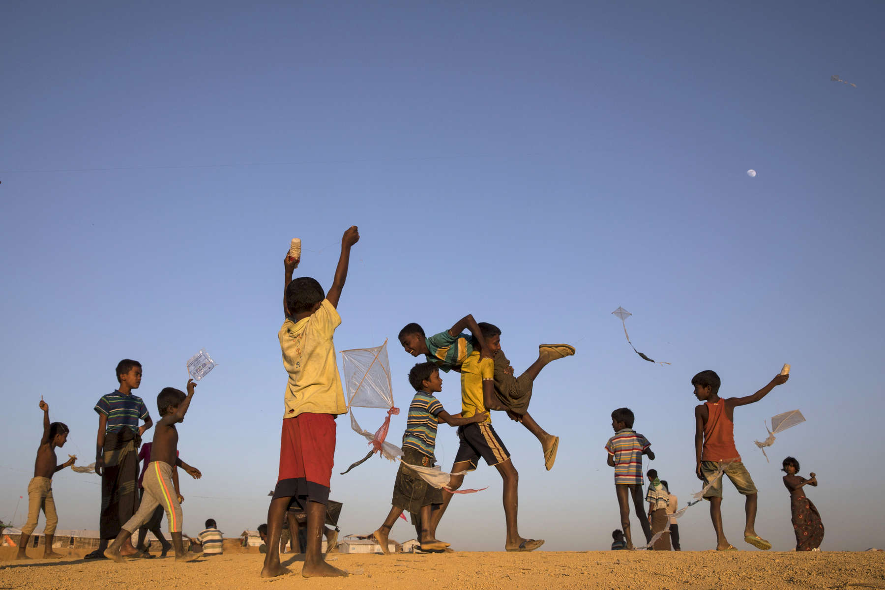 Children fly handmade kites on top of a in Kutupalong camp.