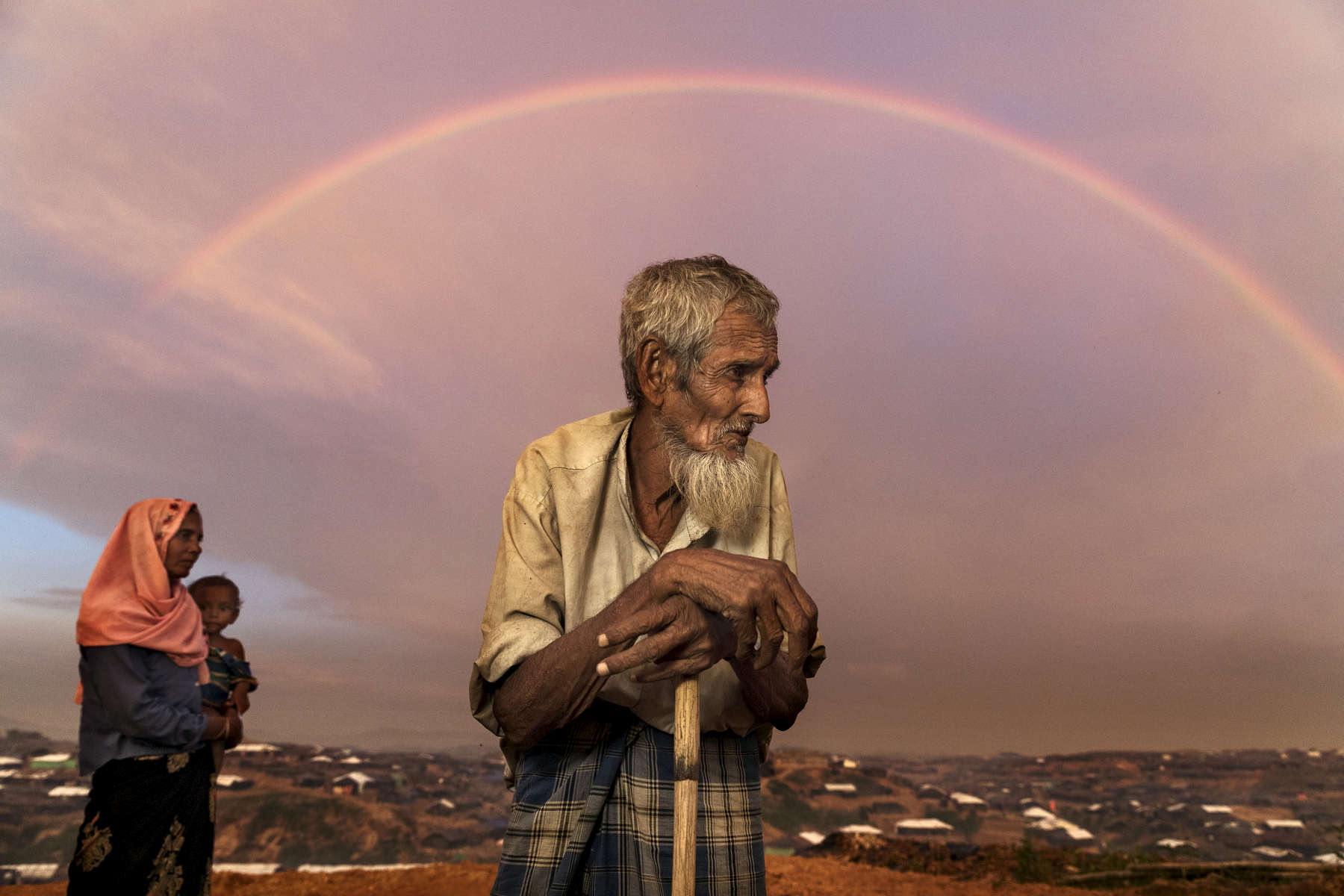 Abu Siddique, 90, stands on a hill overlooking the Kutupalong refugee camp as a rainbow covers the sky. He had to pay people to carry him across the Myanmar border to Bangladesh spending all of his savings.