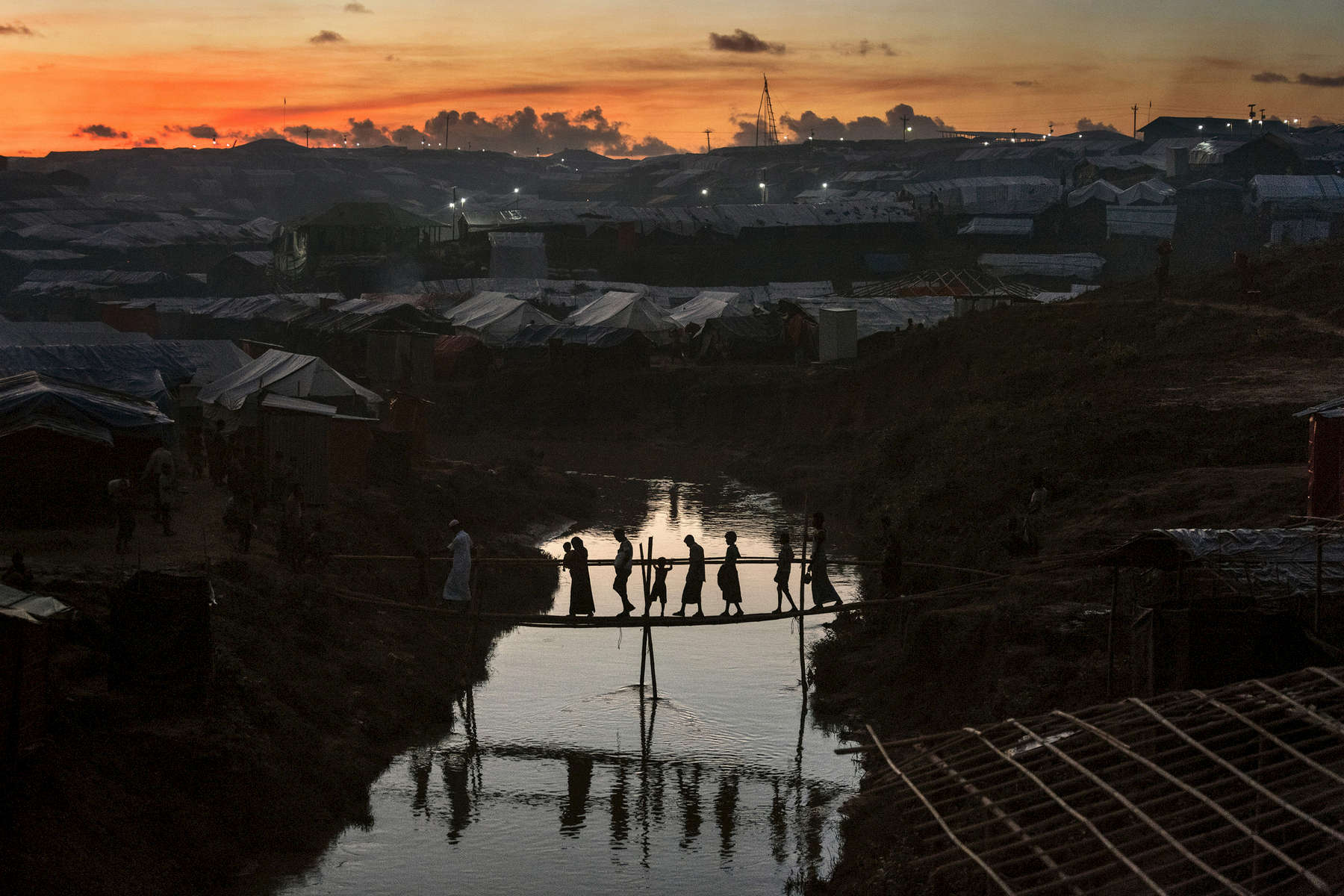 Rohingya cross a bamboo bridge over a stream as the sun sets October 13, inside the sprawling Kutuplaong refugee camp. The refugee emergency unfolded in late August after an attack on state security forces by Rohingya insurgents, triggering a brutal military crackdown that has forced more than half of the country's 1.1 million population fleeing to neighboring Bangladesh creating the fastest cross-border exodus ever witnessed with over 655,000 new arrivals.