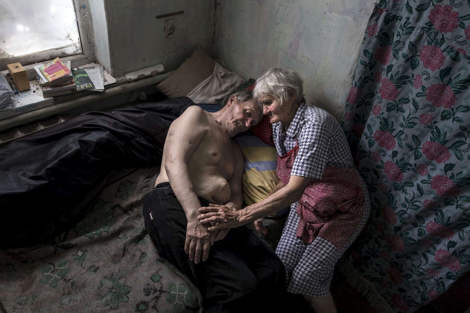 Opytne: Donetsk region: Raisa Petrovna, 80 and her husband Stanislav Vasilyevich live in a village often caught in the crossfire between Ukrainian and Pro-Russian separatists, too close to the contact line. Raisa says that tanks were driving in front of their home in the first year of the war, now they have learned to live with the sound of shelling and gunfire daily.  {quote}We were sitting last home, screaming at them not to kill us!{quote} Riasa said. {quote} Her husband was injured twice by shrapnel, once in his abdomen, requiring surgery. He suffers from a hernia that keeps on growing. Stanislav suffers from dementia now along with his other medical issues. {quote} I have to treat him as a child, I am so sorry that he is like this now, I am afraid to leave him even for a moment.;{quote} Raisa stated. Their two sons live on the other side of the contact line unable to visit often because of the war. Their village, Opytne depends on humanitarian organizations to help the elderly who refuse to leave their homes and are trapped in a dangerous situation.After more than four years of war the armed conflict in eastern Ukraine has a human toll that is staggering. The war has displaced more than 1.6 million with over 2,500 civilians killed and 9,000 injured. Some 200,000 people live under constant fear of shelling every day, with nearly a third of the 3.4 million people in need of humanitarian assistance over 60 years of age. Ukraine has the highest proportion of elderly affected by war in the world.