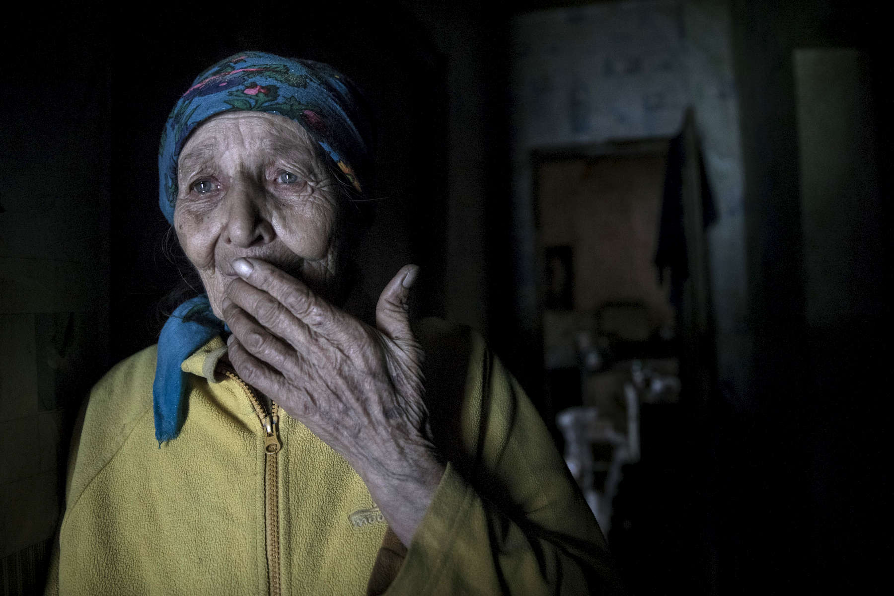 Opytne, Eastern Ukraine:  Mariya Gorpynych, age 76, lives alone. She speaks with tears in her eyes while talking about the death of her son. Victor,48 was killed due to the war in 2016, he was fatally injured by shelling that hit the home. He died in her hands. Her husband, died in the same year from a heart attack  from extreme stress of living too close to the front line. Mariya refuses to leave her village because her family are buried there.{quote}I have nowhere to flee, my whole family is buried here.{quote}  {quote}I got used to the continued shelling.{quote} Opytne is a war torn village on the contact line where only 43 people are left due to the dangers.