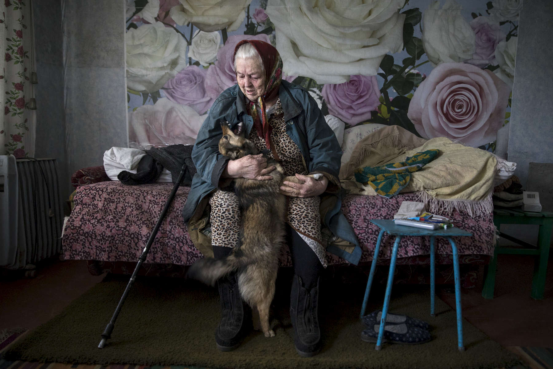 Varvara Arkhipovna, age 81 lives alone on a small pension in Katerinovka, Lugansk region which has a population of less than 300 people as the village is exposed to the sniper fire as the contact line lays just over the hill a few kilometers away. Varvara lives with a puppy that was recently given to her by a health worker in order to improve her mental health as she suffers from depression and high blood pressure. Her family lives in Pervomaisk, a village in Lugansk region on the other side of the front line. She hasn't been able to see her 3 grandchildren in 4 years – since the beginning of the war even though they live only 3 kilometers away.