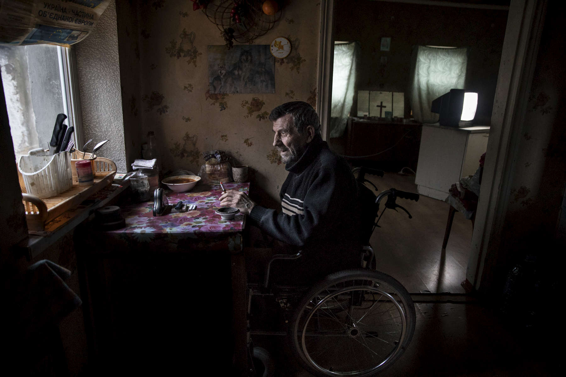 Avdiivka: Vladimir Mamoshyn, age 65, sits in his wheelchair, his wife died in 2010, now he lives alone, his children abandoned him. He resides in the war-torn  Avdiivka village, less than a kilometer from the contact line where daily shelling and gunfire can be heard. In 2016, Vladimir lost his leg due to a vascular disease, with poor access to health facilities along with inadequate health care. After having a heart attack a few months later in 2017 he lost the use of his left hand, now he lives in a wheelchair depending on family and  friends to help him.