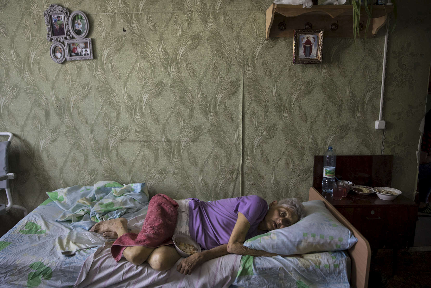 Valentina Iosipovna, age 76 lays in bed waiting for staff to feed her at the Druzhkovka nursing home.