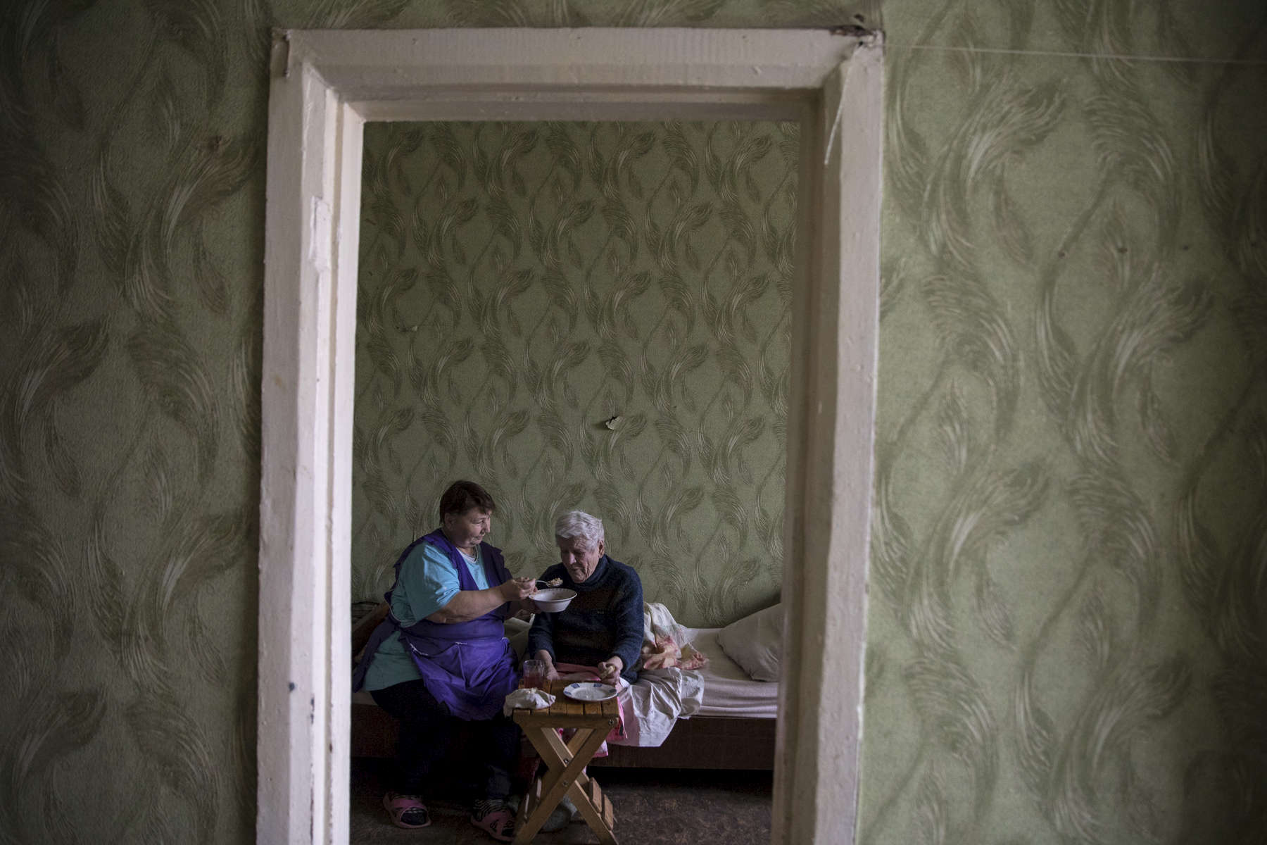 Druzhkovka Nursing home - Donetsk region:An elderly woman gets spoon fed her lunch by staff. The nursing home facility takes care of many elderly who are left behind, and poverty stricken due to the war. After more than four years of war the armed conflict in eastern Ukraine has a human toll that is staggering. The war has displaced more than 1.6 million with over 2,500 civilians killed and 9,000 injured. Some 200,000 people live under constant fear of shelling every day, with nearly a third of the 3.4 million people in need of humanitarian assistance over 60 years of age. Ukraine has the highest proportion of elderly affected by war in the world.