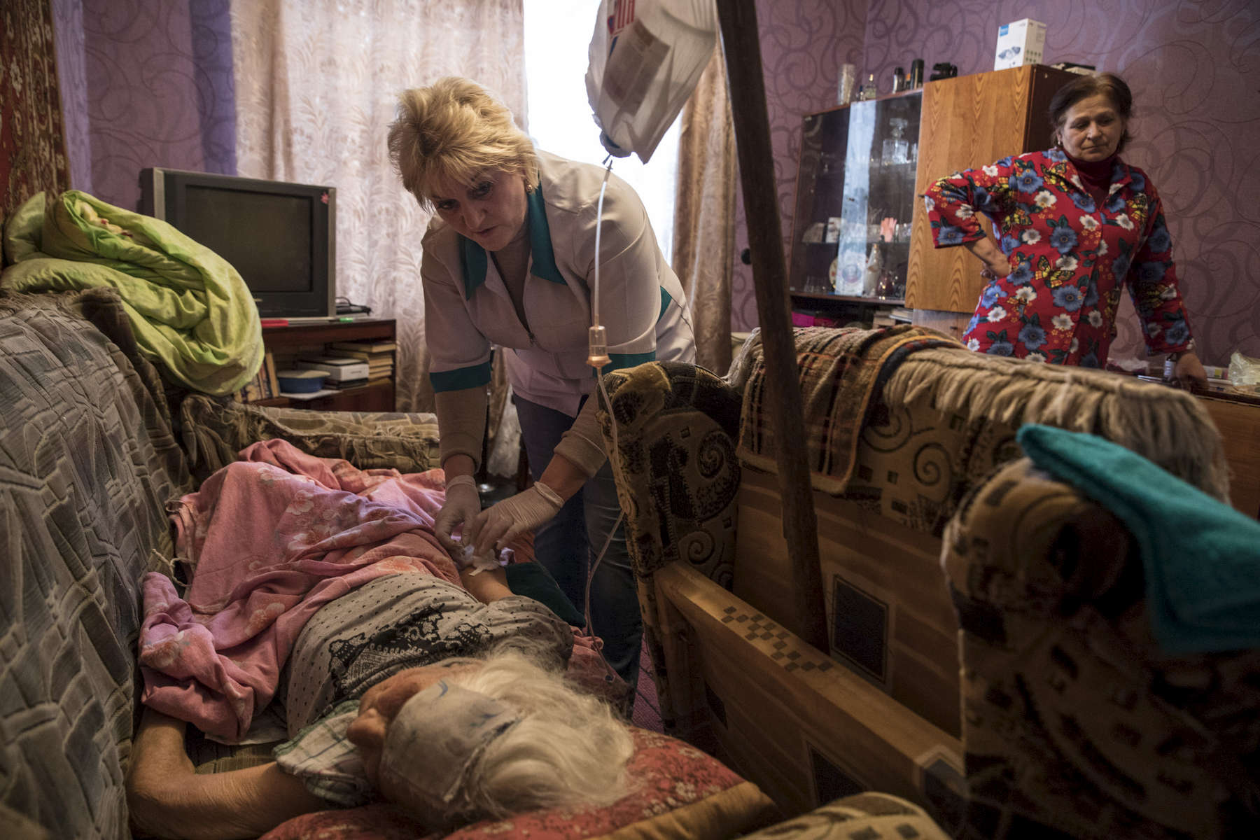 Mayorsk, Donetsk regionAntonina Malna, age 84, gets cared for by a local nurse, she had a stroke a few months ago and remains in a comatose state while her daughter Zoya watches. The nearest hospital is 25 km away and cannot afford to provide 24h care for patients like Antonina due to the lack of medical staff. Mayorsk is right on the border area in Eastern Ukraine, a very difficult location for the elderly to be unless they have medical and family support.