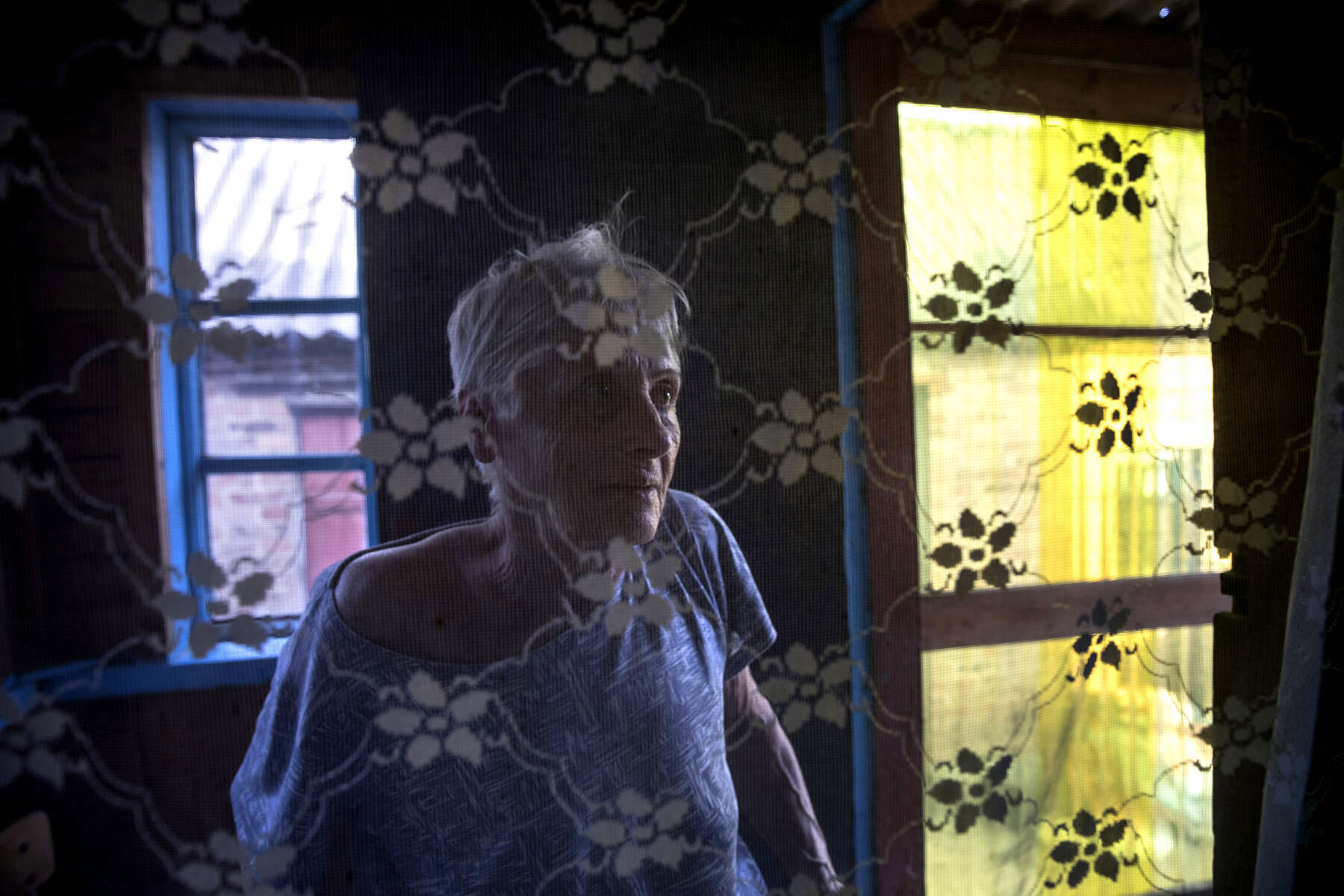 Chasov Yar, Donetsk region: Lyudmila Yevgenievna, age 64  from Chasov Yar is seen by windows at a residence for the elderly in Chasov Yar, Eastern Ukraine. All her relatives have died and she was left alone .Evgeniy Tkachev has founded the elderly care facility with his own money. He bought two private houses across the street from each other. One house is for elderly women, another for men. {quote}I evacuate elderly people from the stress affect by the conflict.{quote}These people have nowhere to go. Over 50% of the elderly here do not receive their pensions due to the loss of the documents.