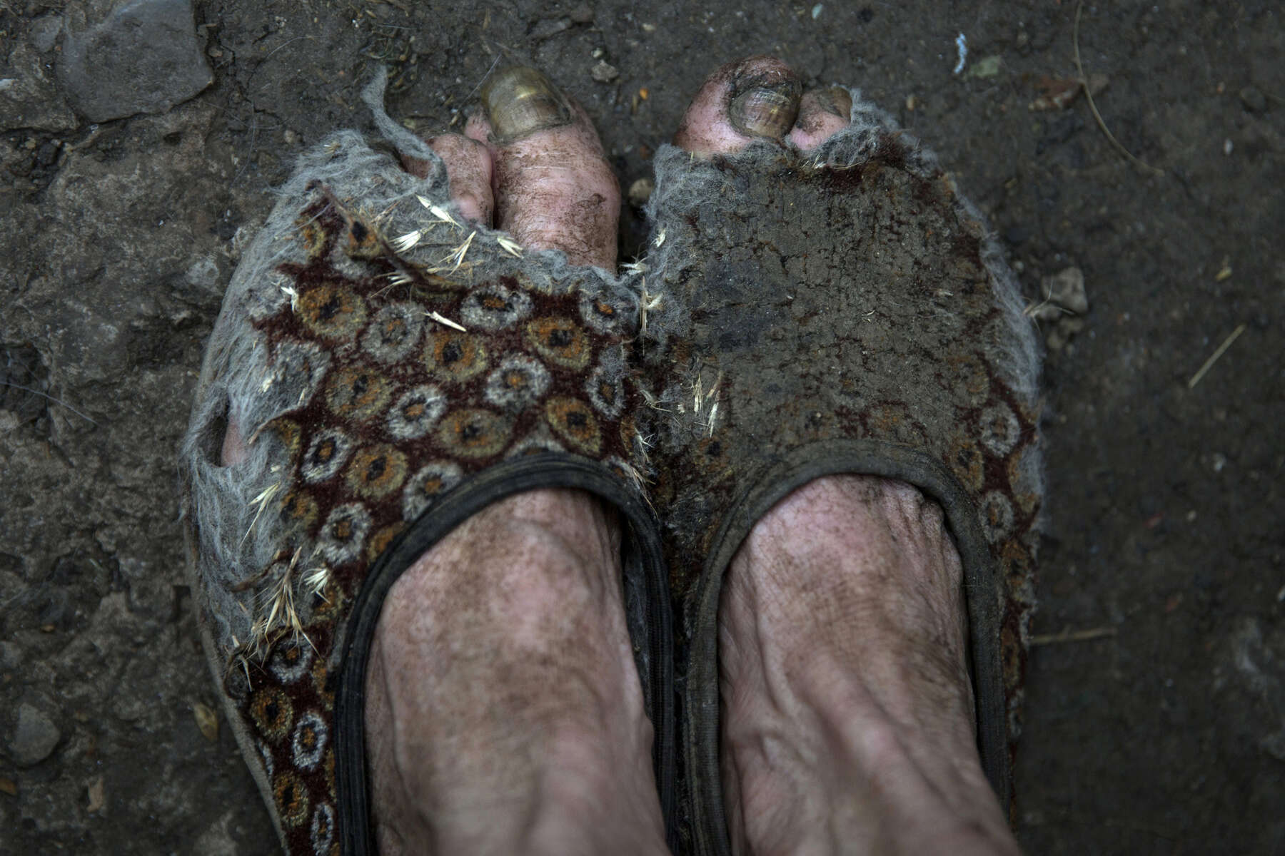 Opytne: Donetsk region: Raisa Petrovna, 80 can't afford new shoes so she wears the same old slippers every day. Raisa Petrovna, 80 and her husband Stanislav Vasilyevich live in a village often caught in the crossfire between Ukrainian and Pro-Russian separatists, too close to the contact line.