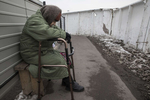 Mayorsk : An elderly handicapped woman rests after trying to walk the long distance in the cold to cross the border from Donetsk to the government-controlled territory of Ukraine in order to collect her pension. There is no regular wheelchair assistance when crossing the border area.