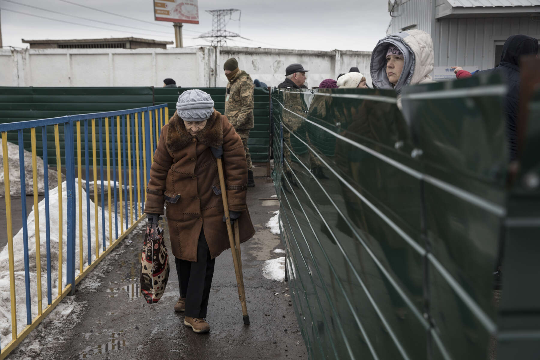 Mayorsk, Ukraine: An elderly handicapped woman slowly makes her way along the border crossing to Donetsk after making the exhausting journey to get her pension in Eastern Ukraine.