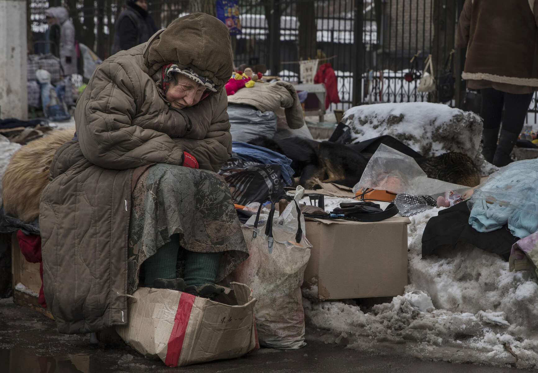 Donetsk, People's Republic (DPR) : Galina Mikhailovna , age 79, waits for customers at a second hand market in suffering during a cold winter day in February. She sells used goods that others give to her in the market for pensioners, sits in the snow with some street dogs. She has no pension, she never went to Ukraine to register, claims she can'Äôt afford to travel to the other side every 57 days which is required by the government. She is in  debt so can't afford to pay for heat and water in her apartment anymore.