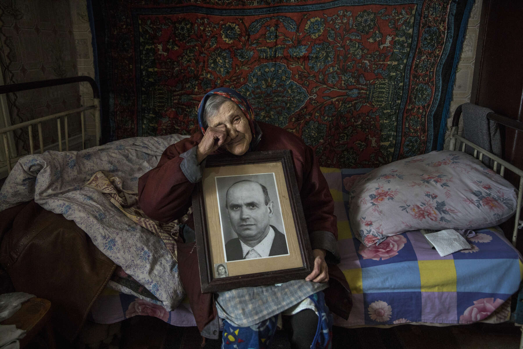 Katerinovka, Lugansk: Natalia Reshetnyakova, age 83 holds a portrait of her late husband who she was married to for over 50 years. She lives alone now. The only thing left reminding her of her husband is this portrait. The population of Natalia's village comprises less than 300 people. The village is exposed to the sniper's fire as the contact line is just few kilometers away.