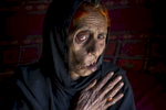 KABUL, AFGHANISTAN - APRIL 10, 2015:  Widow Naiz Bibi claims she is 68 but really can\'t remember clearly.  She has had a very hard life,  blinded in one eye she fled up north to the IDP camps of Kabul from the war torn province of Helmand. Naiz  barely survived after she lost 7 members of her family during a NATO air strike including her husband, daughter and 2 sons. The eight that survived  are now helping to take care of her since she is in bad health, living in the squalid Nasaji Bagrami camp outside of Kabul for thousands of war refugees.