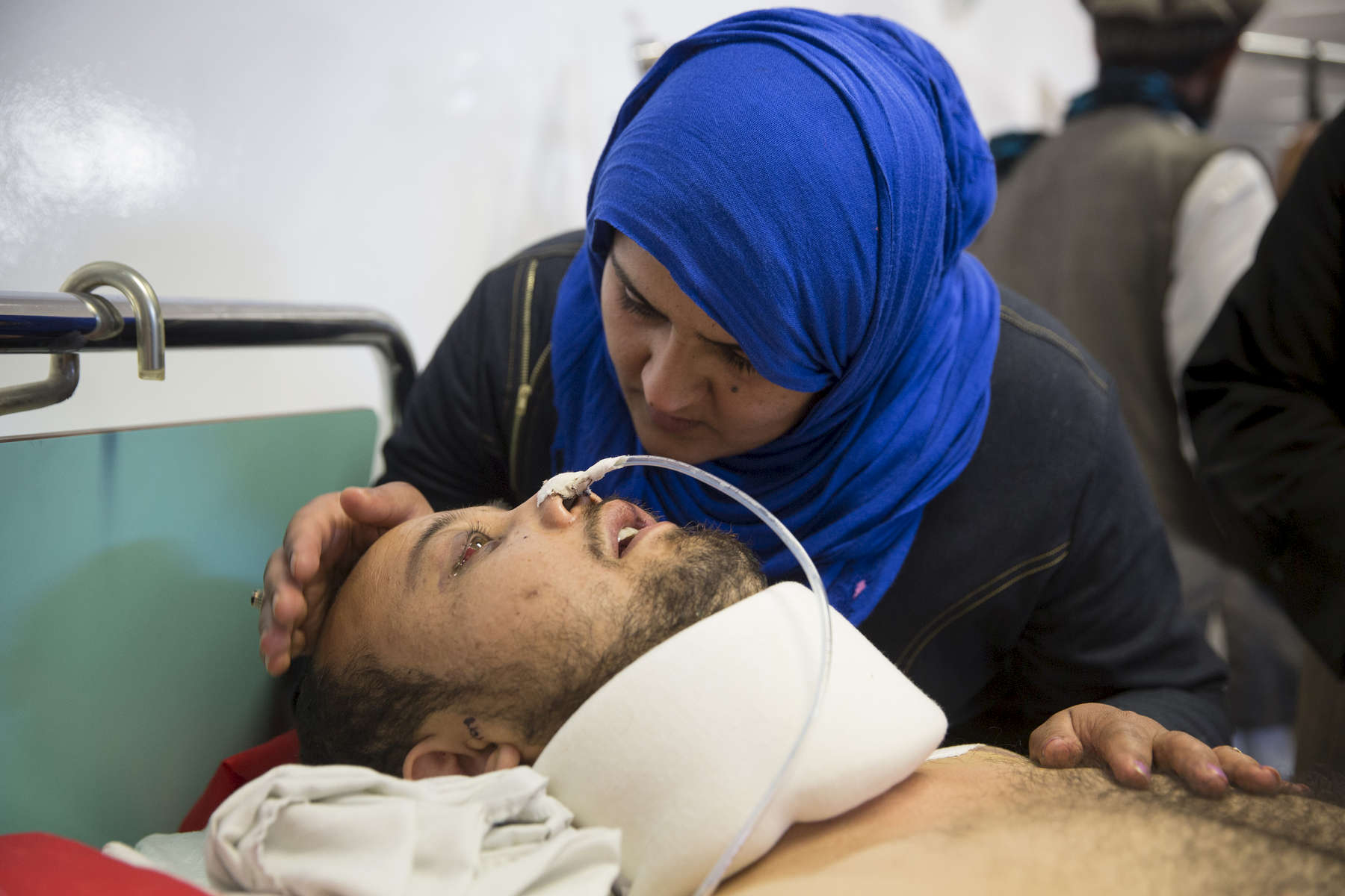 KABUL, AFGHANISTAN -MARCH 21, 2016: Azim, 25, a a quadriplegic who suffered bullet wounds to his face and shoulder gets visited by his wife Shokoria for the first time at the Emergency hospital in Kabul on March 21, 2016. Every year the UN comes out with their report documenting the unfortunate carnage from America's longest and most costly war in history. Along with the price tag estimated in the hundreds of billions, the human toll from a 2015 UN Assistance Mission To Afghanistan (UNAMA) report stated the number of Afghan civilians killed and wounded surpassed 11,000.  which was the deadliest on record for civilians in Afghanistan since the US-led invasion more than 14 years ago.