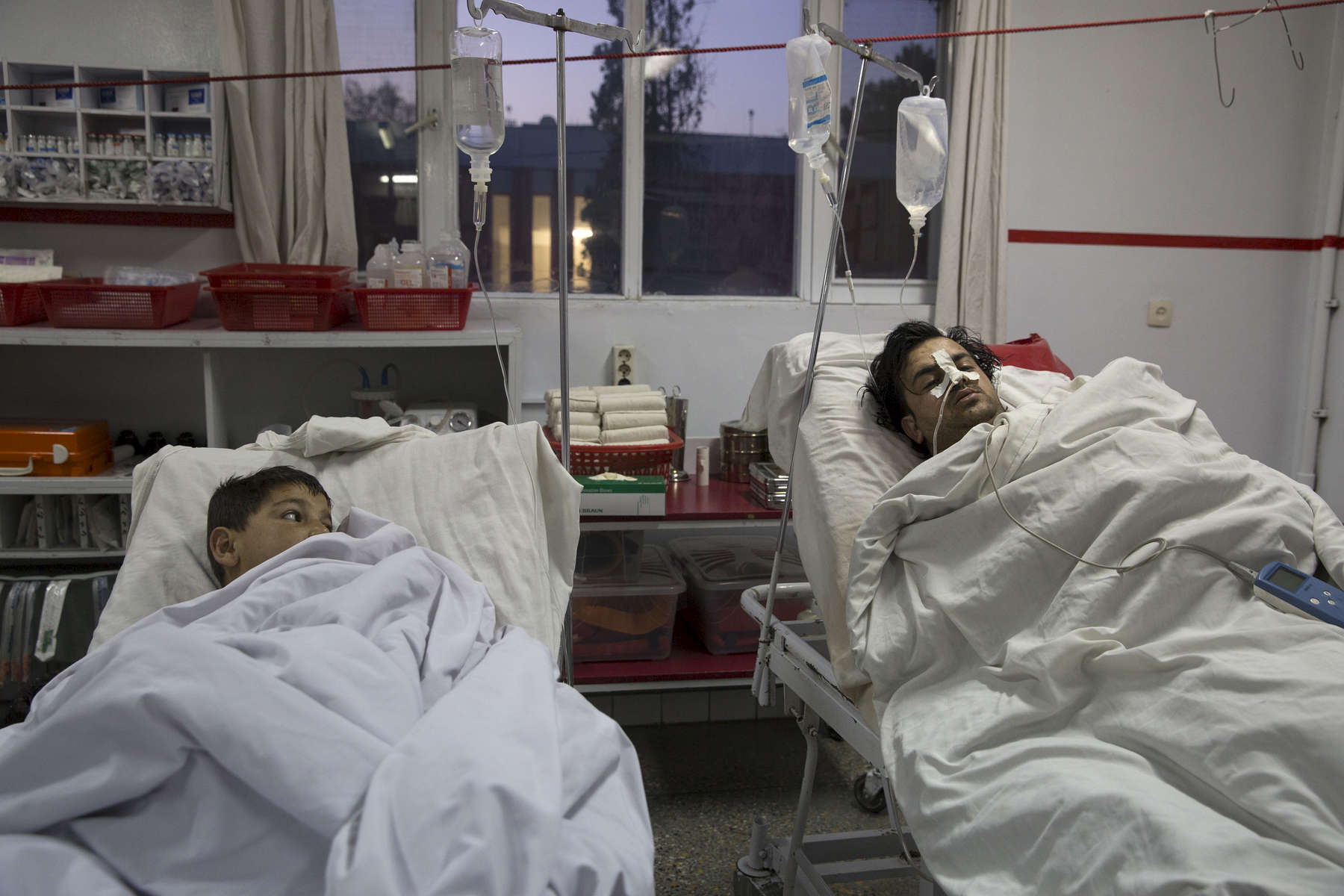 KABUL, AFGHANISTAN -MARCH 21, 2016:  Kabul on February 28, 2016. In the emergency room a boy over at another patient getting treatment at the Emergency hospital in Kabul. Every year the UN comes out with their report documenting the unfortunate carnage from America's longest and most costly war in history. Along with the price tag estimated in the hundreds of billions, the human toll from a 2015 UN Assistance Mission To Afghanistan (UNAMA) report stated the number of Afghan civilians killed and wounded surpassed 11,000.  which was the deadliest on record for civilians in Afghanistan since the US-led invasion more than 14 years ago.