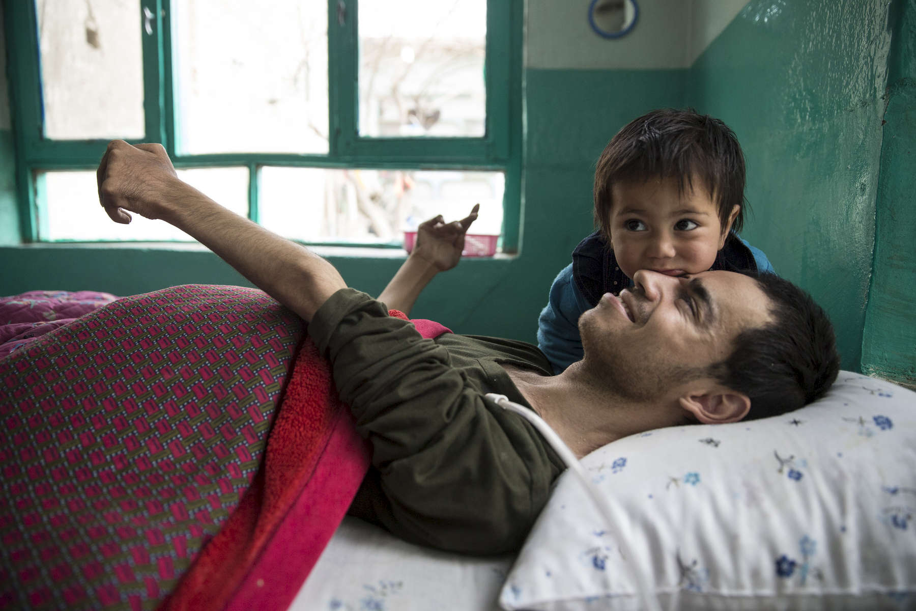 KABUL, AFGHANISTAN -MARCH 22, 2016:  Khuja Fareed, 24, a quadriplegic enjoys some time with his niece Roksar, 3 and a half years,  at his home in Kabul on March 22, 2016. He is now a quadrapalegic injured while delivering supplies to a military base truck driver for the US military until he was shot in the neck during fighting between the Taliban and the US military. With no financial help from the US military or the Afghan government Khuja depends on his family to care for him.Every year the UN comes out with their report documenting the unfortunate carnage from America's longest and most costly war in history. Along with the price tag estimated in the hundreds of billions, the human toll from a 2015 UN Assistance Mission To Afghanistan (UNAMA) report stated the number of Afghan civilians killed and wounded surpassed 11,000.  which was the deadliest on record for civilians in Afghanistan since the US-led invasion more than 14 years ago.