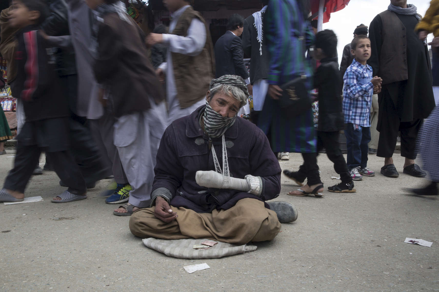 KABUL, AFGHANISTAN -MARCH 20, 2016: Ibrahim, a mine victim begs on the street during the Afghan New Year festival hoping that many would have sympathy in Kabul on March 20, 2016. Many handicapped who are unemployed become beggars. Afghan civilians are at greater risk today than at any time since Taliban rule. According to UN statistics, in the first half of 2016 at least 1,600 people had died, and more than 3,500 people were injured, a 4 per cent increase in overall civilian causalities compared to the same period last year. The upsurge in violence has had devastating consequences for civilians, with suicide bombings and targeted attacks by the Taliban and other insurgents causing 70 percent of all civilian casualties.