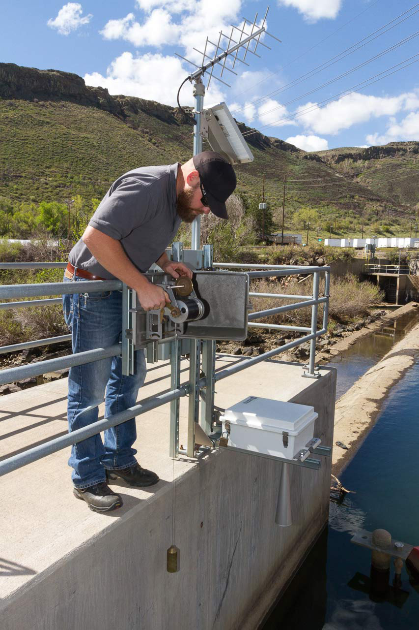 Client: Headwaters Magazine Summer 2017. Project Details: Photograph Jason Smith, water commissioner for District 7 of the South Platte Basin, on location during a normal day. Photo Editor and Photo: Paula GillenDetails: Jason Smith, water commissioner for District 7 of the South Platte Basin, checks a stream gauge on Clear Creek. Smith lowers a drop weight into the water to ground truth the remote reading he receives by computer.