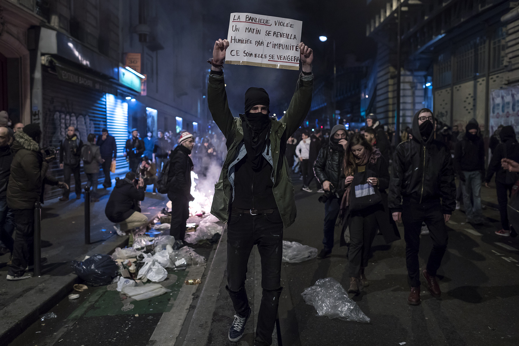 A young man holds up a sign reading {quote}The raped suburb woke up one day humiliated by impunity. Tonight it will take revenge.{quote} at Barbes station in Paris, France on Feb. 15, 2017.