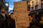 A young man holds up a sign reading {quote}Who protects us from the police?{quote} at Barbes station in Paris, France on Feb. 15, 2017.