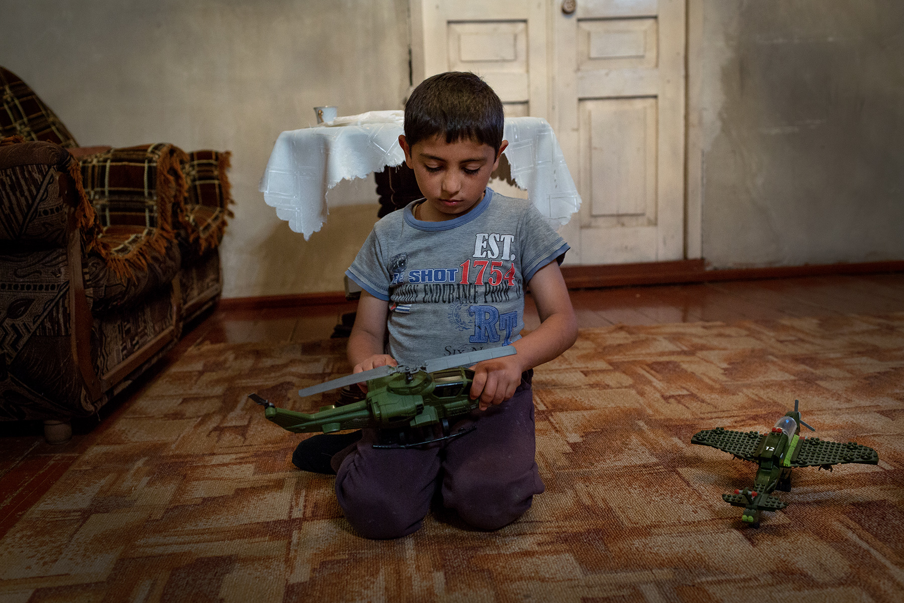 Albert, 7, plays with military toys while his parents watch the Victory Day Military Parade in Moscow on tv in a living room of Bagaran (Shirak), an Armenian village on the Turkish border on May 9, 2018