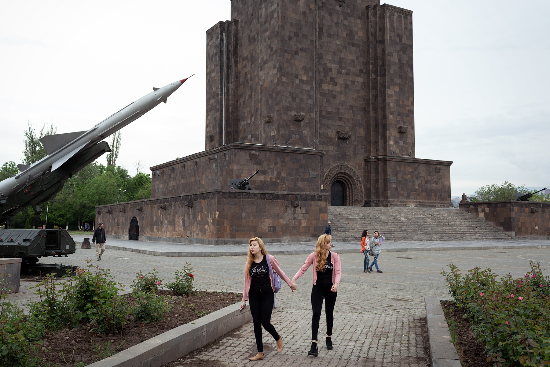 Twin girls walk in front of a soviet SA-2 missile exposed in the Victory park of Yerevan on May 6, 2018