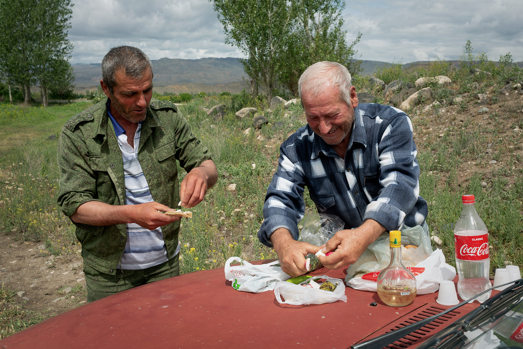 Father and son have a snack and a drink of schnapps after working in the fields in Bagaran (Shirak), a small Armenian village on the Turkish border.