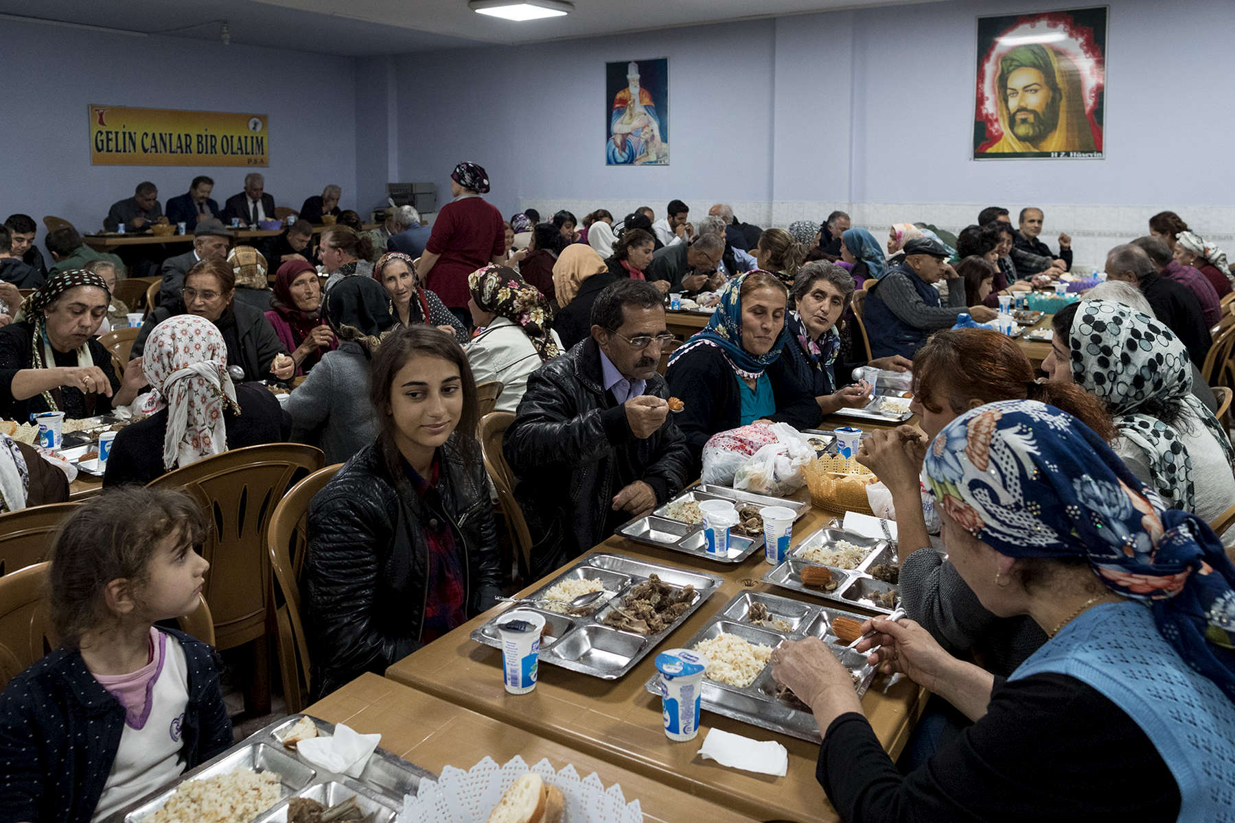 Turkey, 2017 - Alevis share a meal after a {quote}cem{quote}. On the wall, the figure of Ali, son-in-law of Mahommet and founder of the sect. Branch of Shia Islam and Sufism, officially ignored by the Turkish authorities. They have no juridical recognition in Turkey.