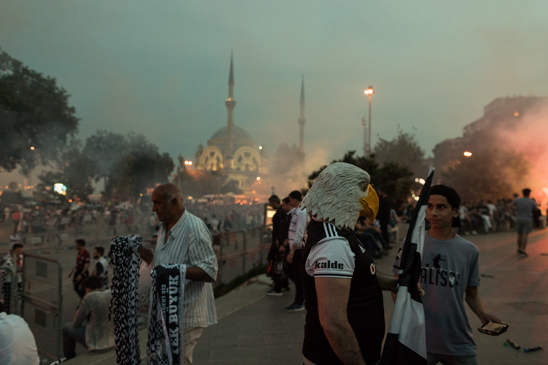 A Besiktas supporter is seen with an eagle mask, symbol of the club, as supporters leave the stadium to celebrate the Turkish Super League title after the last match of the season against Osmanlispor, near the Vodafone Park stadium in Istanbul, Turkey, Saturday, June 3, 2017.