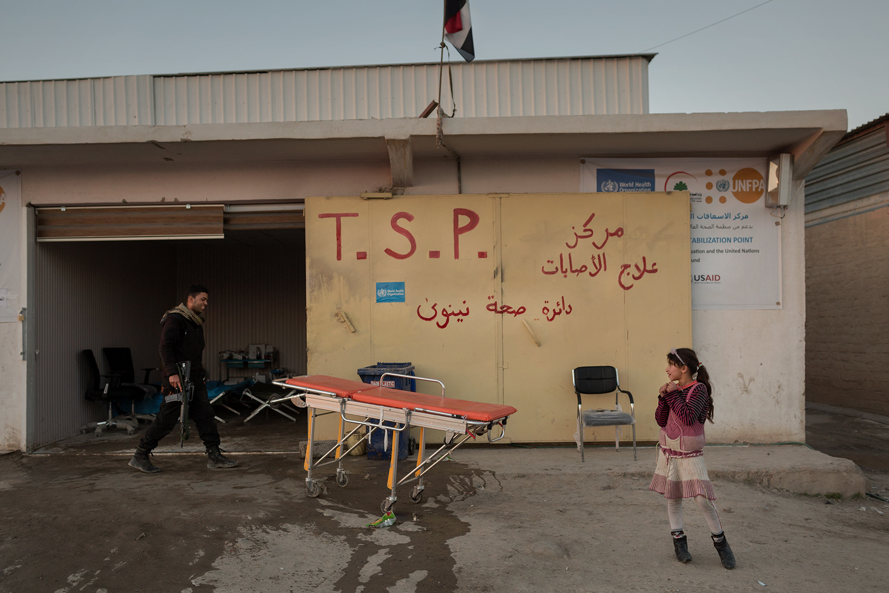A young girl stands in front of the Medical Advanced Post of Gogjali as a man with a gun walks behind at the entrance of Mosul, Iraq on Jan. 5, 2017. This station and a Medecins Sans Frontieres station on the side are the only medical posts from Mosul to the Khazir displaced center, 40 km away.