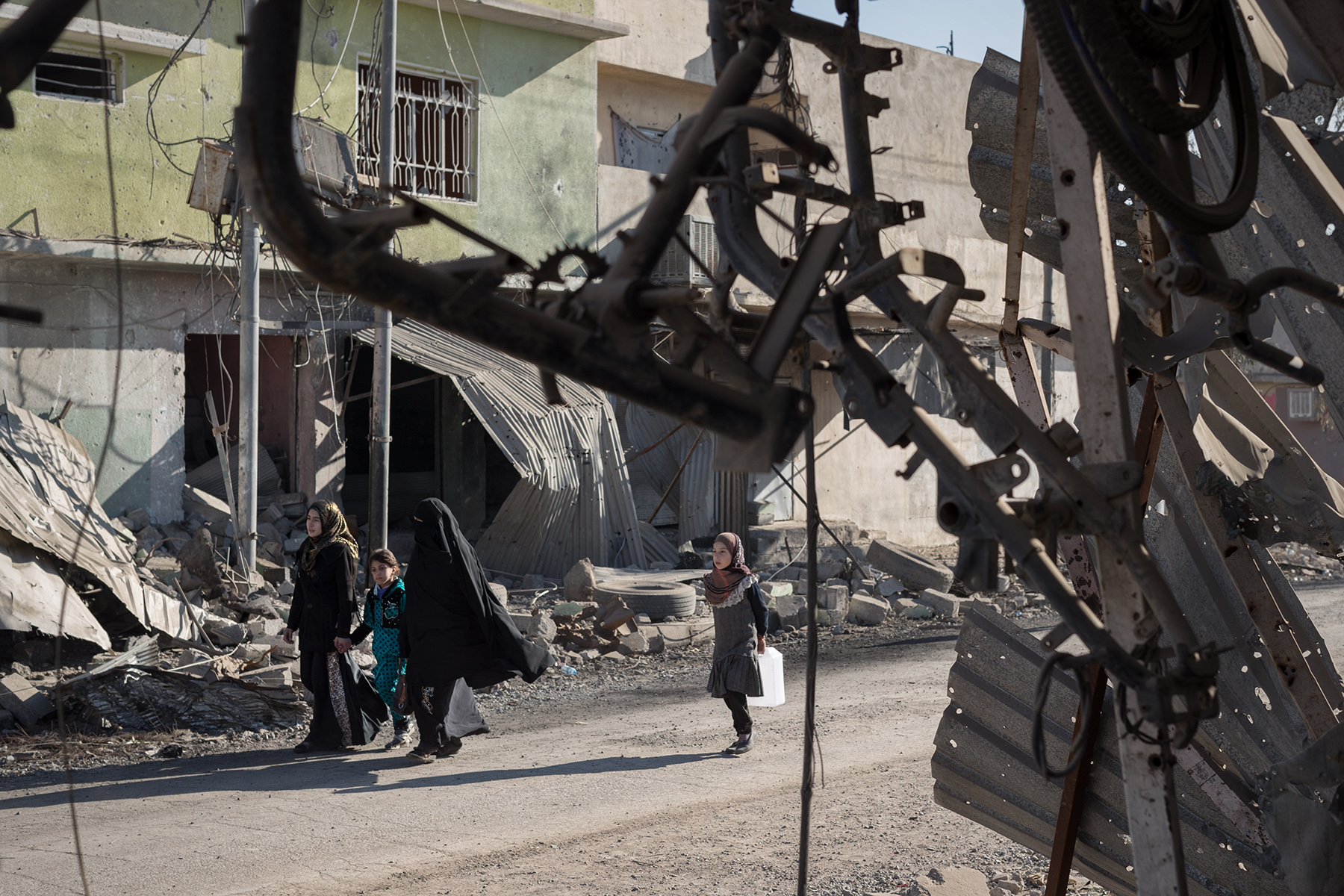 Women and girls walk ahead the remains of a two-wheeled shop in Al-Quds neighborhood, liberated three days before. Mosul, Iraq on Jan. 6, 2017.