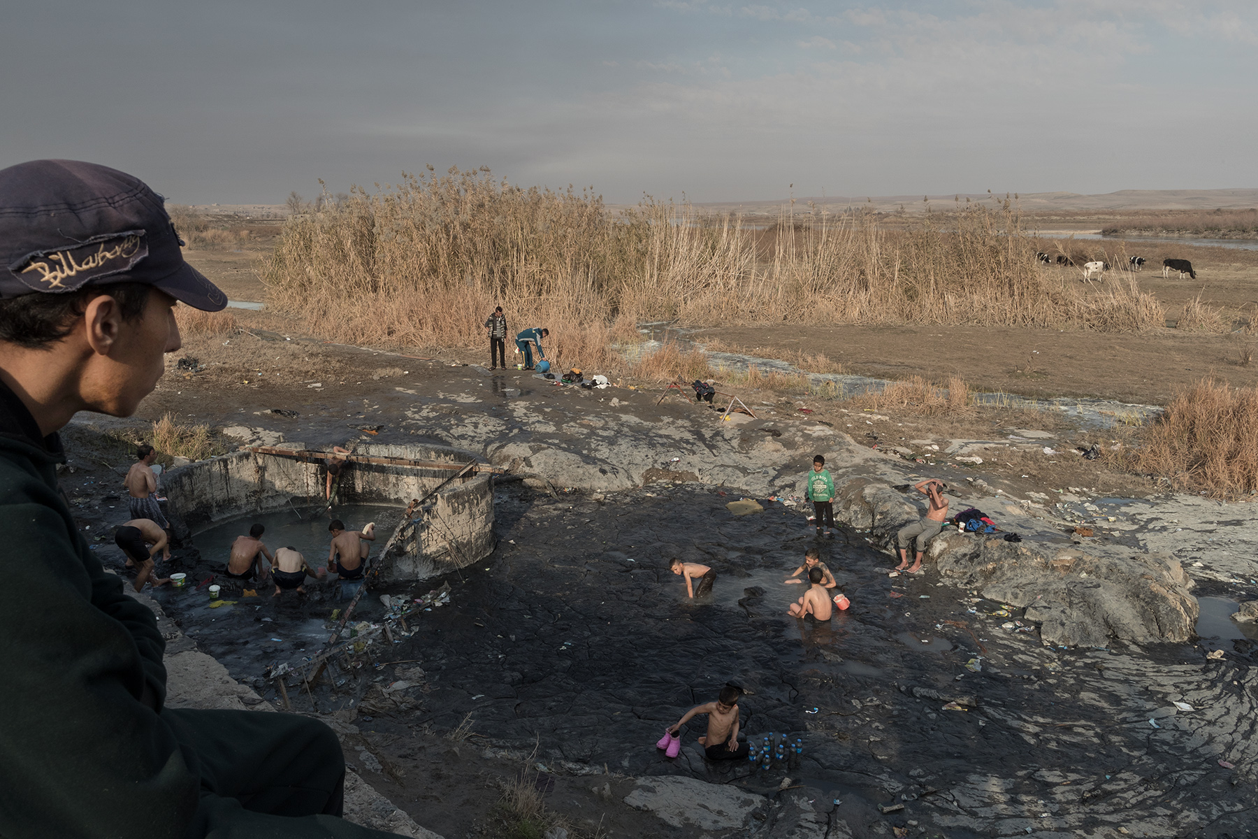 Sulphured waters smoke in concrete vats on the edges of the Tiger, in the thermal city of Hammam al-Alil, Iraq on Jan. 8, 2017. Men and boys gather there to wash themselves and to play.