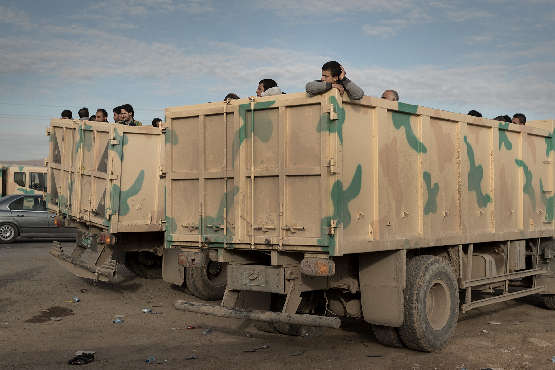 Iraqis displaced from Mosul wait in military trucks to be transferred to various camps. Bartella, Mosul, Iraq on Jan. 7, 2017.