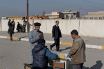 In front of Hammam al-Alil Court, a public writer fills fills the documents for the judge. Iraq on Jan. 9, 2017. In the background military secure the area.