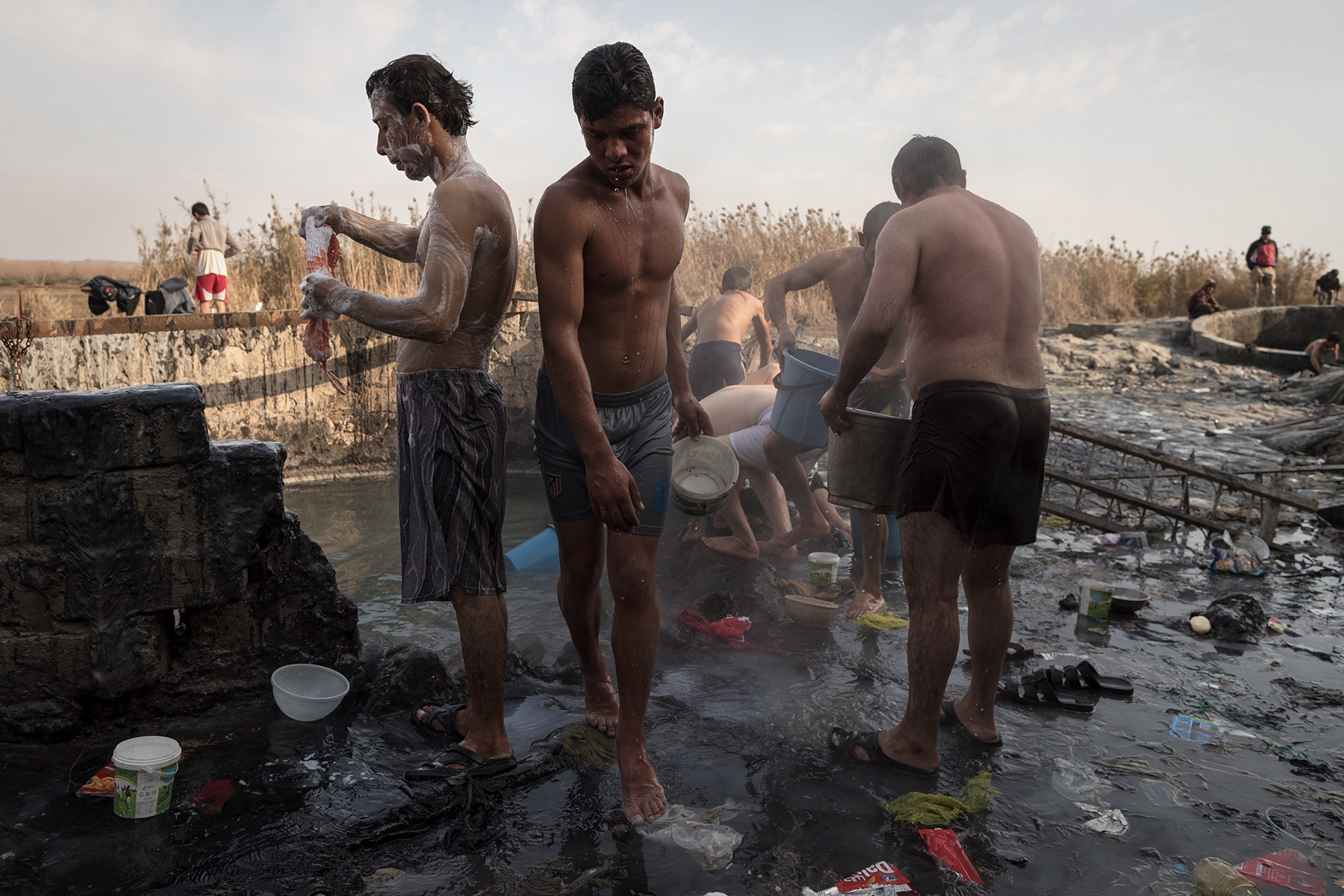 Sulphured waters smoke in concrete vats on the edges of the Tiger, in the thermal city of Hammam al-Alil, Iraq on Jan. 8, 2017. Men and boys gather there to wash and to relax themselves.