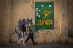 Men walk on the pavement in front of a painted logo of Juwa on Thursday, June 18, 2015 in Mutsamudu, Anjouan. The political party of former president of Comoros Ahmed Abdallah Sambi won the last legislative elections in February 2015 and prepares the candidature of Sambi for the 2016 presidential election.The country is facing many problems as unemployment, water and electricity shortage and constantly delaying salary payment.