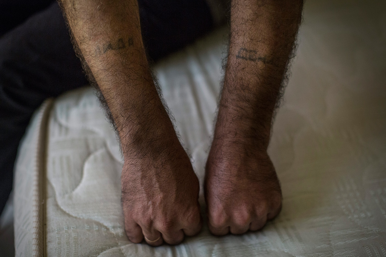 Tammam, a Syrian refugee who had a restaurant in Homs shows his tattoos with the names of his wife and his son he made himself. They took different directions to flee their homeland. The only wish of Tammam is to go back in a more safe Syria. Mamoudzou, Mayotte, France. Tuesday, June 16, 2015