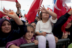 Young female supporters show the 'rabia sign' during an electoral rally of AKP's candidate Recep Tayyip Erdoğan in Istanbul on June 17, 2018