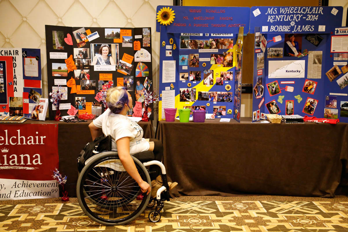 A visitor reads about the contestants; each woman creates a display table and board about her life and work, including awards, volunteer work, news clippings and occasionally information about the circumstances that led to her disability.