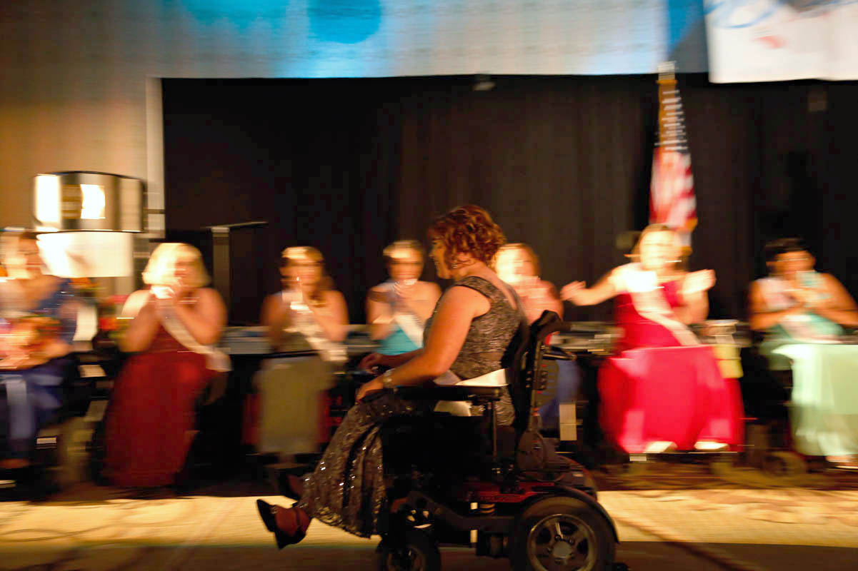 Kelsey Kleimola, Ms. Wheelchair Michigan 2014, whizzes past the line of contestants in her motorized wheelchair. Long Beach, CA. August 9, 2014.