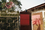 Barbed wire and a plastic chair top the wall around a home in Kenema, a town known for its diamond wholesale business.