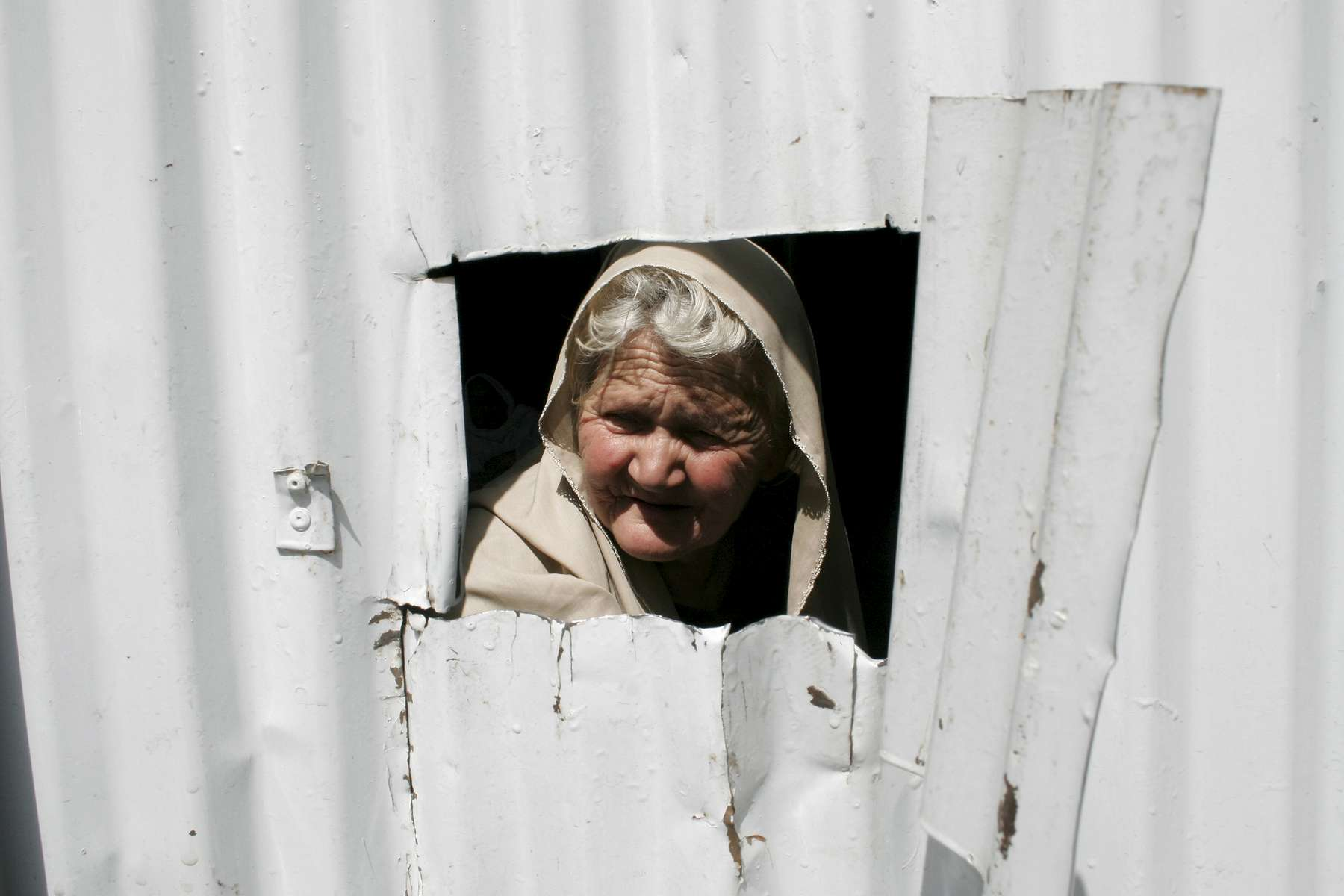A woman peers through an opening in the gate that leads into Rabia Balkhi Women's Hospital, the second busiest maternity hospital in Kabul.