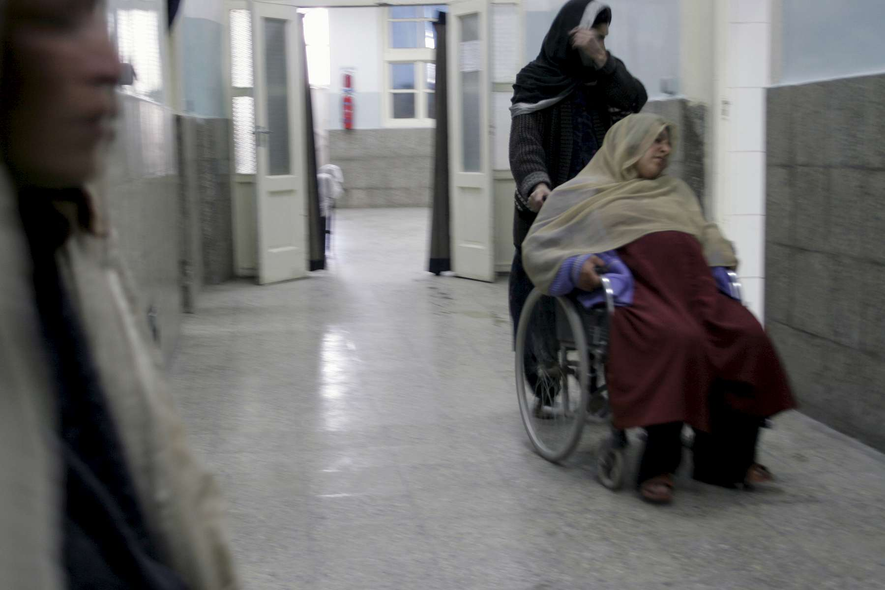 A woman is wheeled down the corridor, headed for the delivery room. As many as 30 to 40 children are born a day at the hospital.