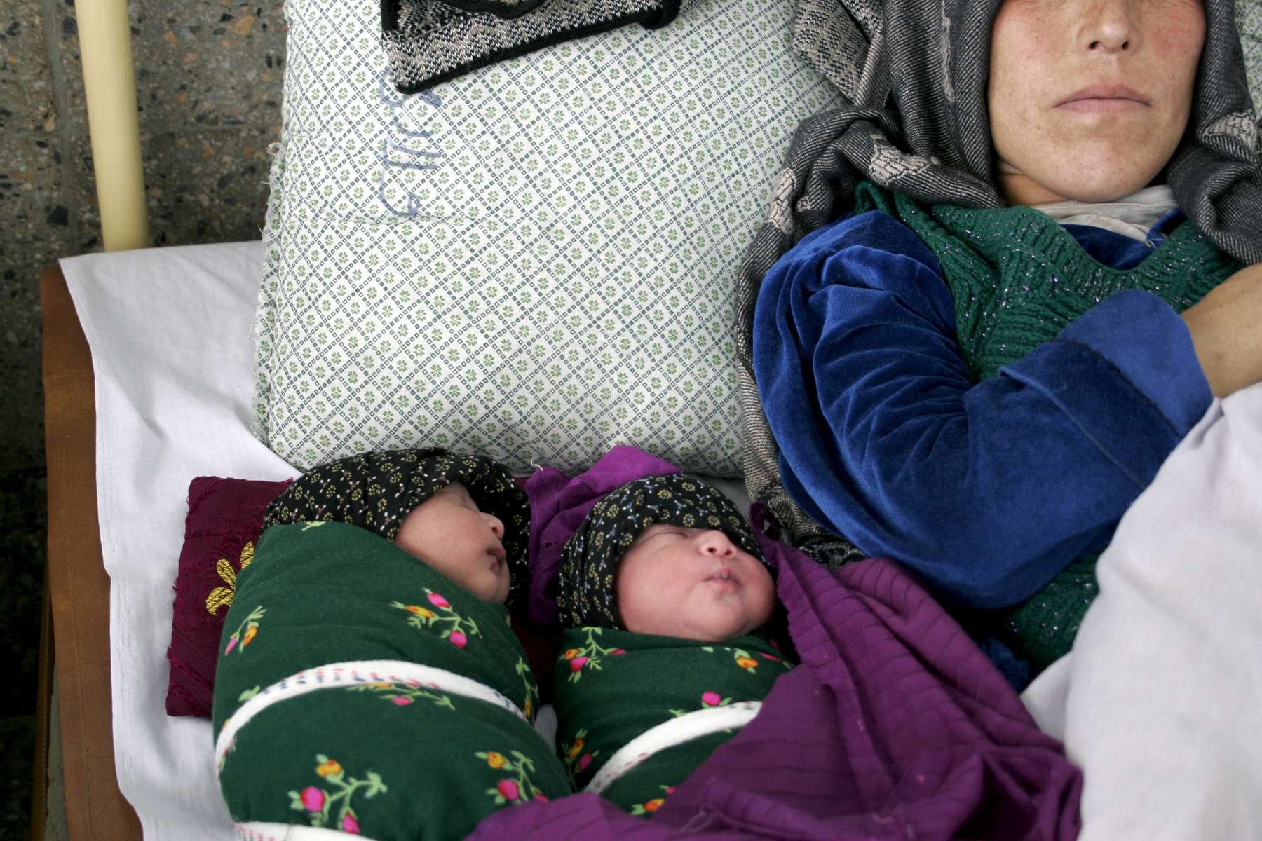 A mother rests next to her twins, born a few hours earlier. More than 12,000 babies a year are delivered at Rabia Balkhi. The fertility rate for Afghan women is 6.6, two and a half times higher than the world average.