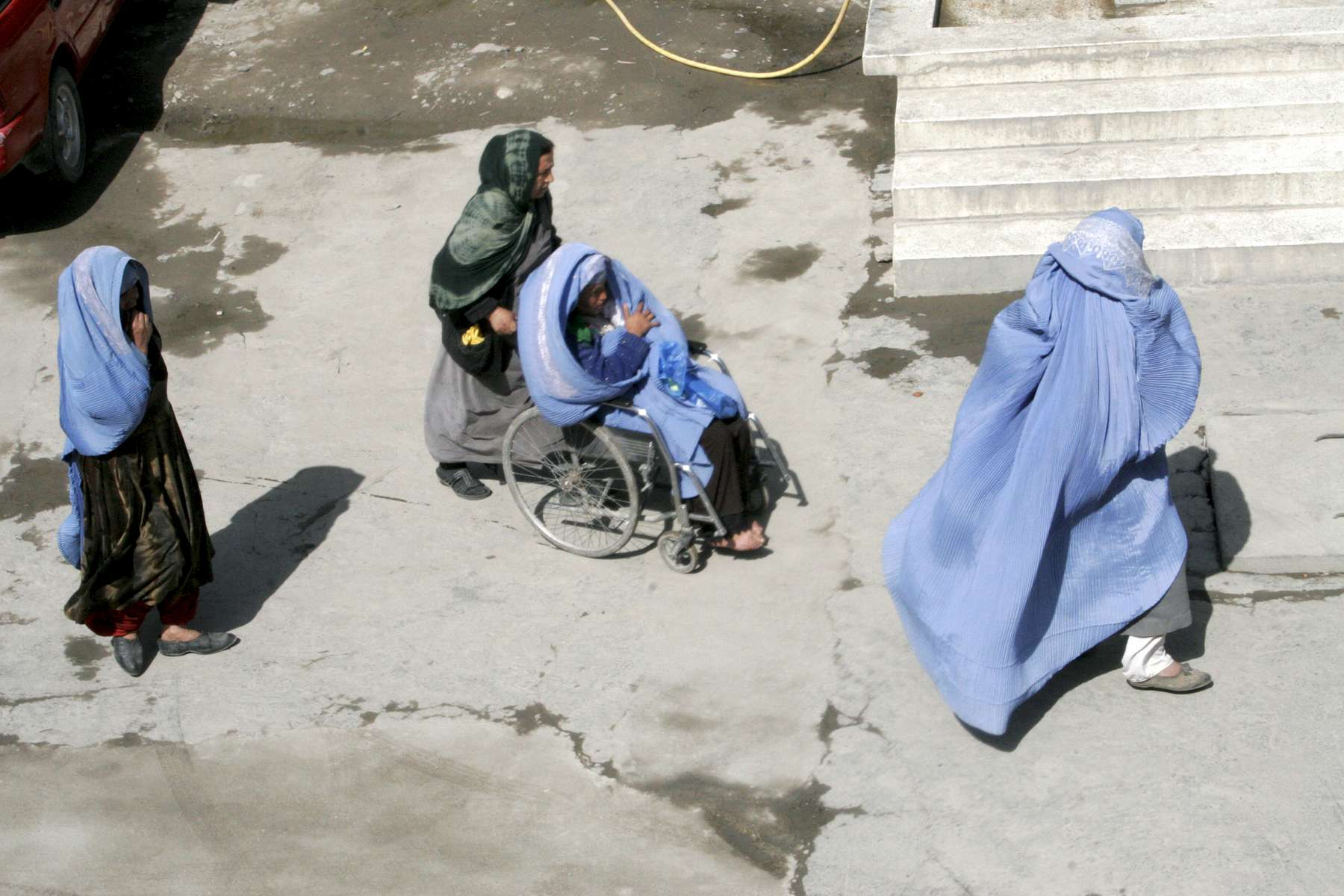 A new mother is taken by wheelchair to the front gate of the hospital, where her relatives will put her in a taxi and take her home. Most women leave the hospital within a few hours of giving birth.