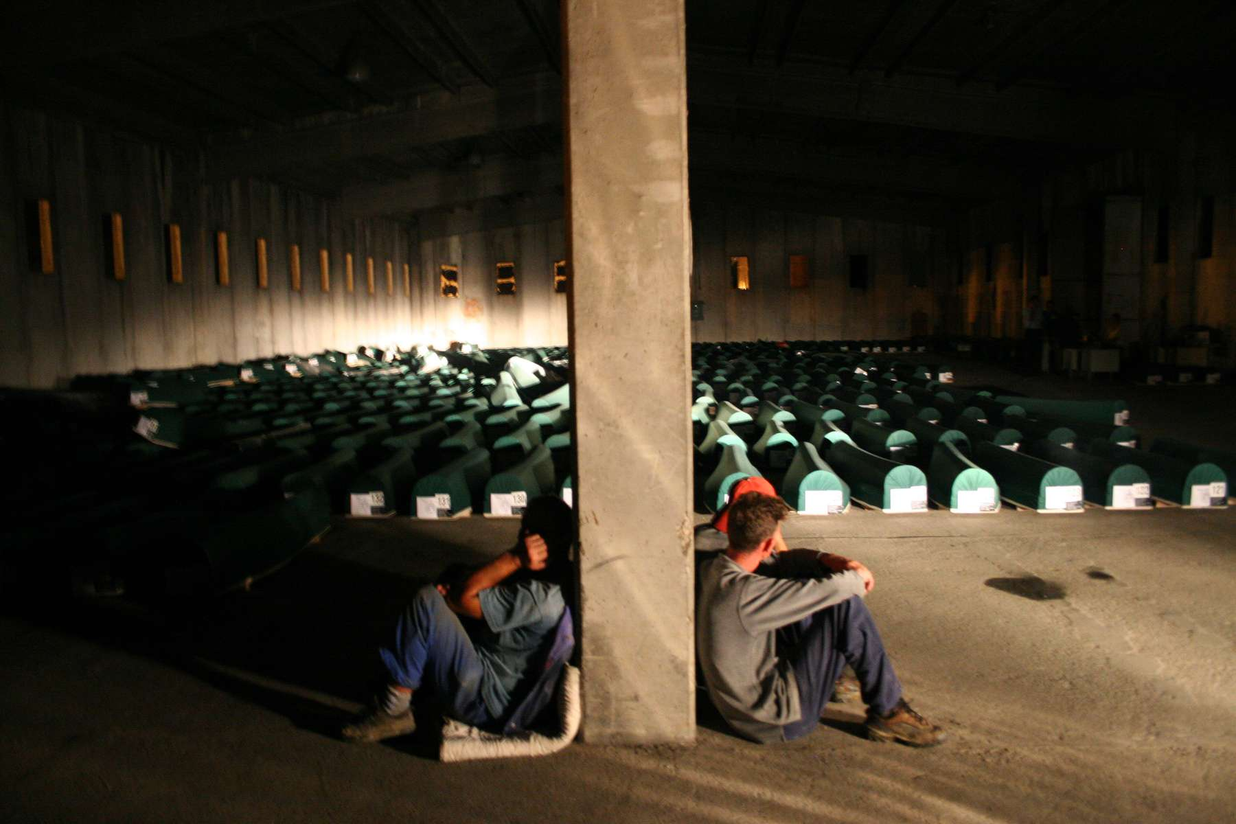 Workmen take a break from moving more than 600 tahuts, traditional Muslim coffins, from a warehouse to the site of the Srebrenica memorial across the road, where they will be buried as part of the July 11 commemoration ceremonies marking the tenth anniversary of the massacre. With only the light cast by car headlights to guide them, the men will work all night.