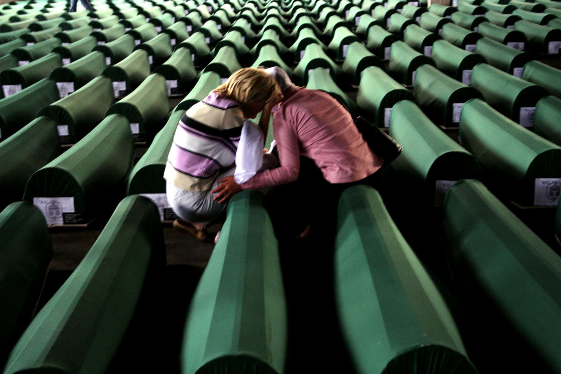 A woman crying over the coffin of a family member is comforted by a friend, among rows of tabuts, or traditional Muslim coffins, containing the remains of more than 600 men and boys who will be buried at the Srebrenica memorial site on July 11. The burial will mark the tenth anniversary of the massacre of some 7,000 to 8,000 Muslim men and boys at the hands of Serb forces during the 1992-95 war. The killings were the worst genocide in Europe since the end of World War II.