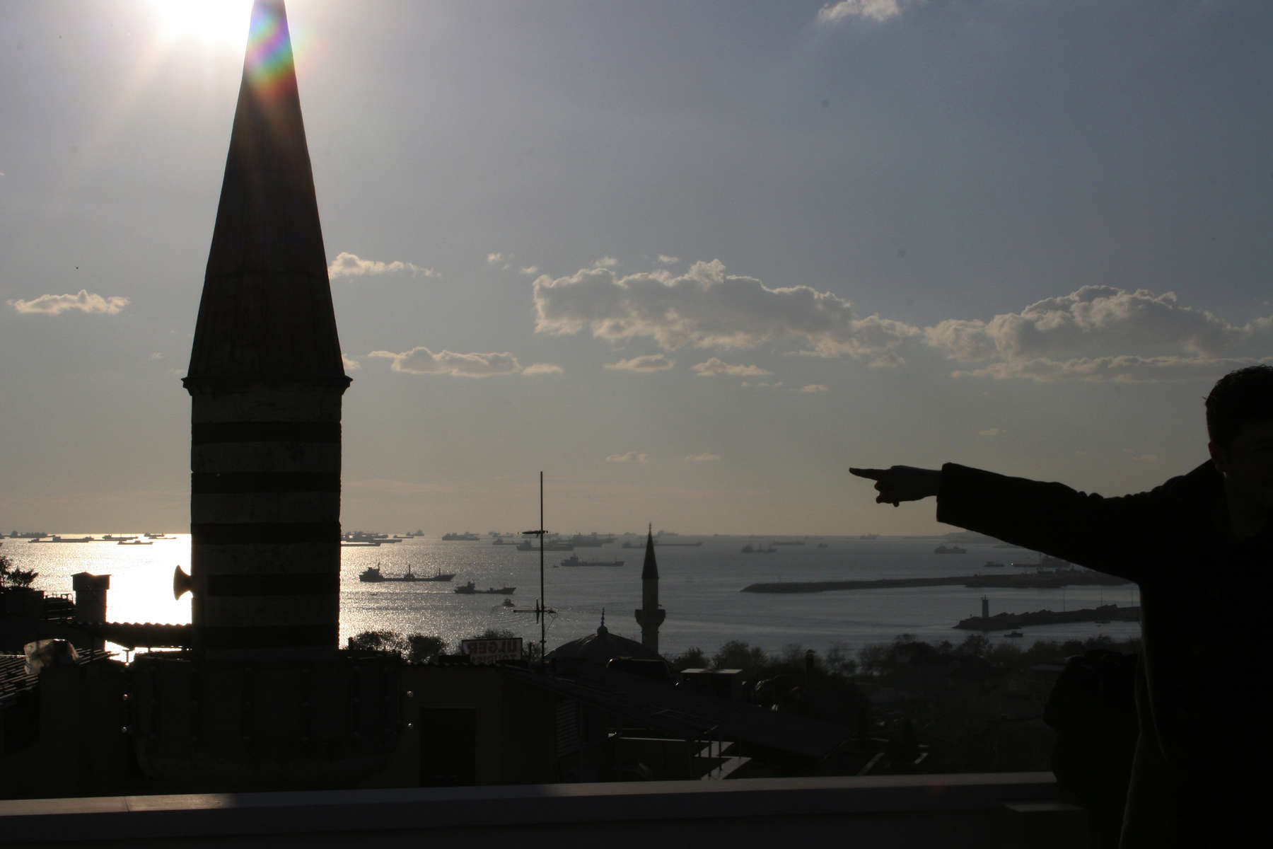 With the minaret of a mosque in the foreground, a man standing on a rooftop in the old Sultanahmet neighorhood of Istanbul points at the numerous freighters that constantly ply the Marmara Sea as they prepare to head up the Bosphorus Straits to the Black Sea.