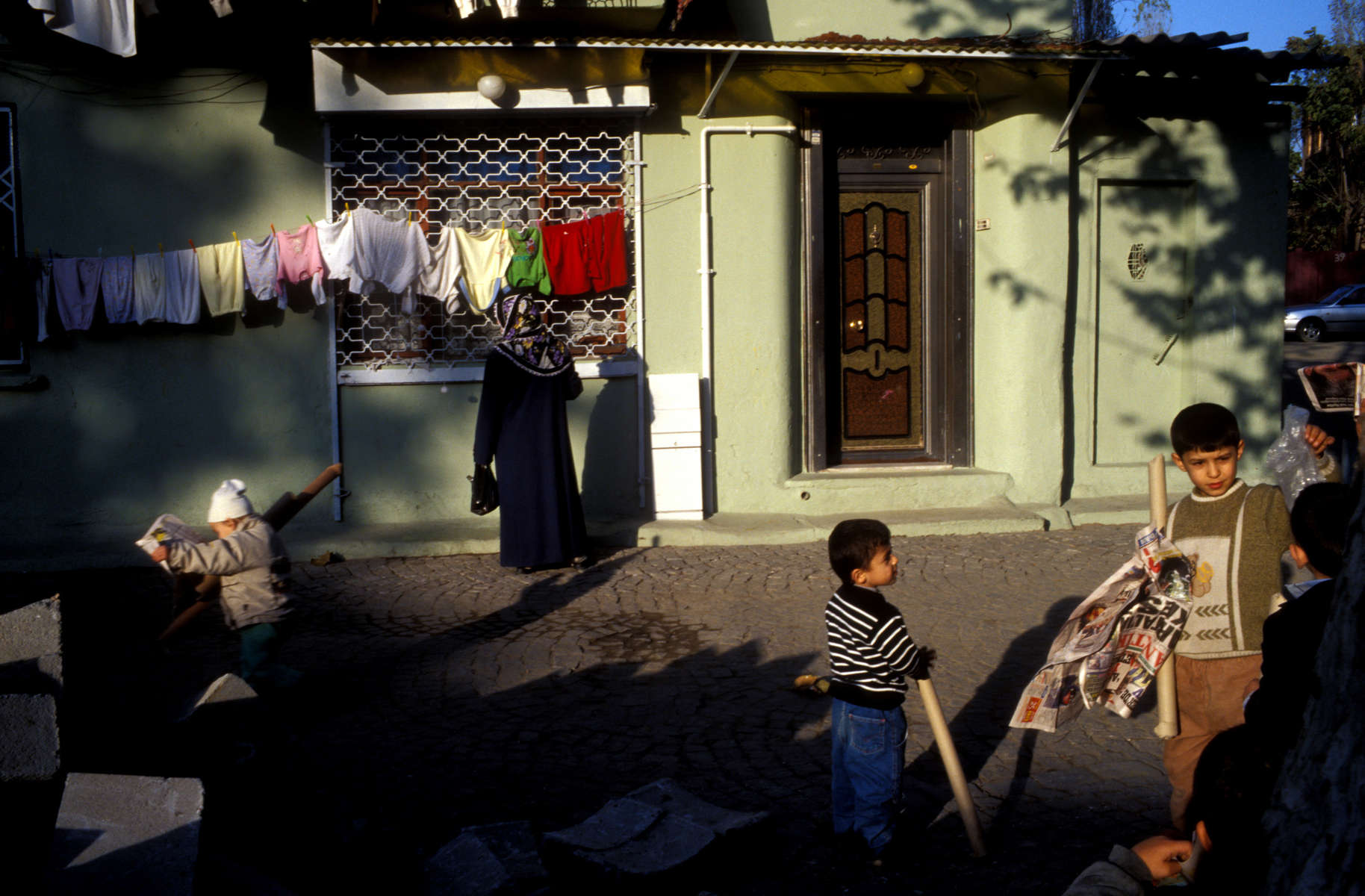 Children play while a scarved woman waits for a friend to come to the door in the religiously conservative working class neighborhood of Zeyrek in Istanbul.